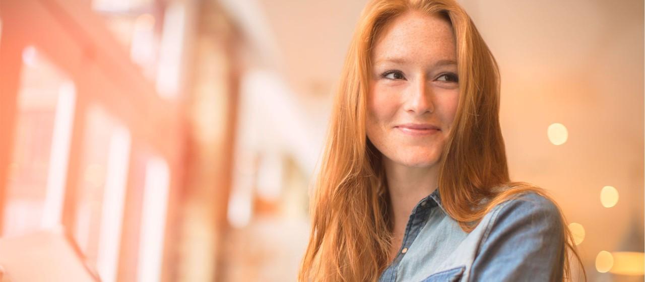 Junge Frau mit roten Haaren die lächelt