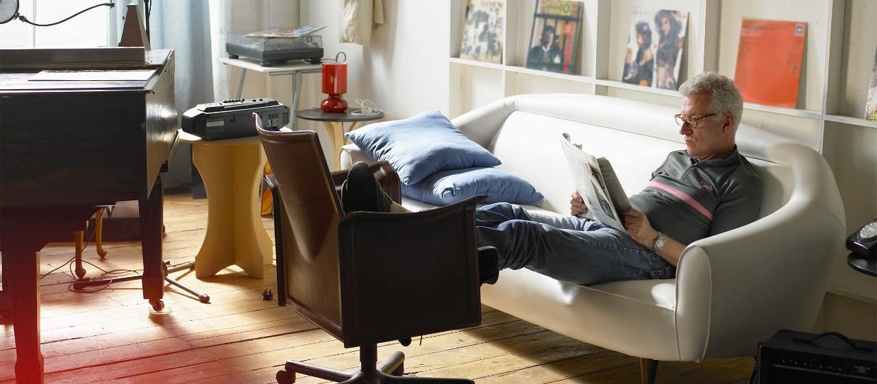 Älterer Mann mit Zeitung auf Couch