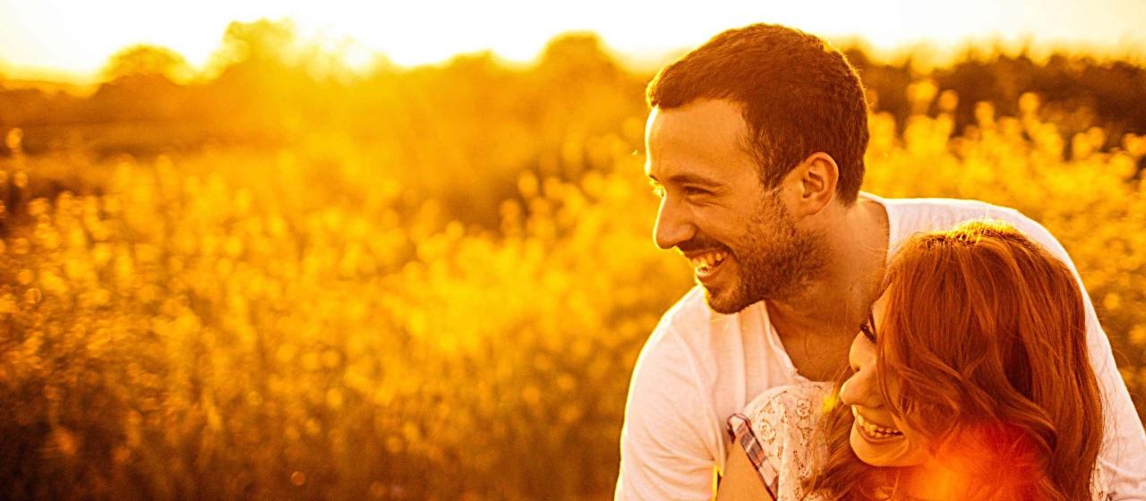 Junges Paar im Sonnenuntergang auf einer Wiese