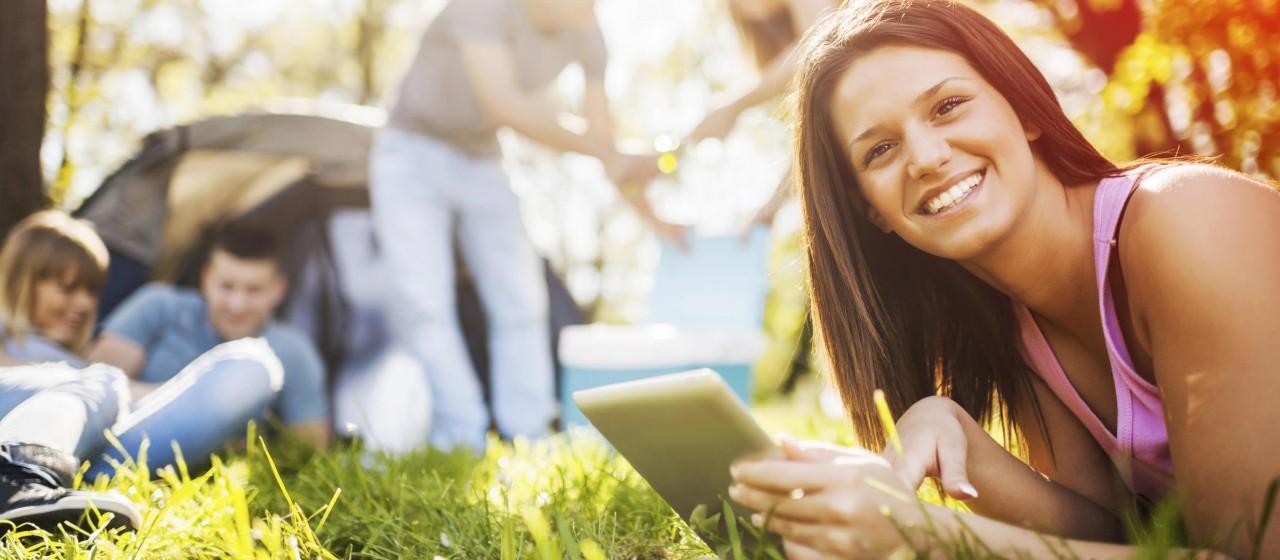 Junge Frau liegt im Gras und schaut auf ihr Tablet.