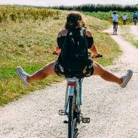 Lachende junge Frau parkt am Meer und schaut aus dem Seitenfenster ihres Autos