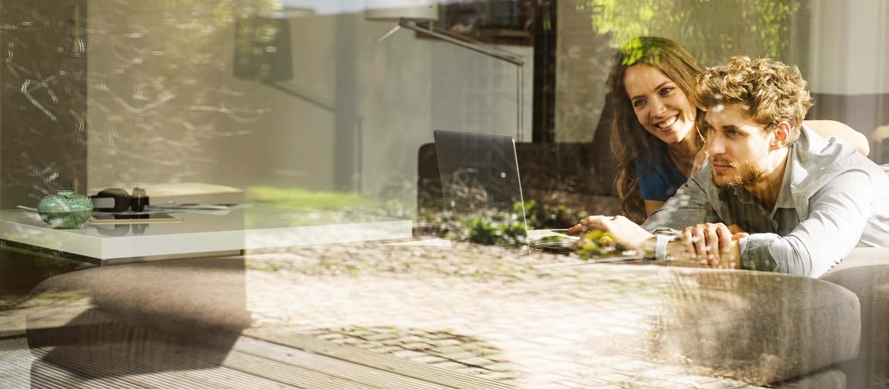 Junges Paar spielt im Garten mit der Schubkarre