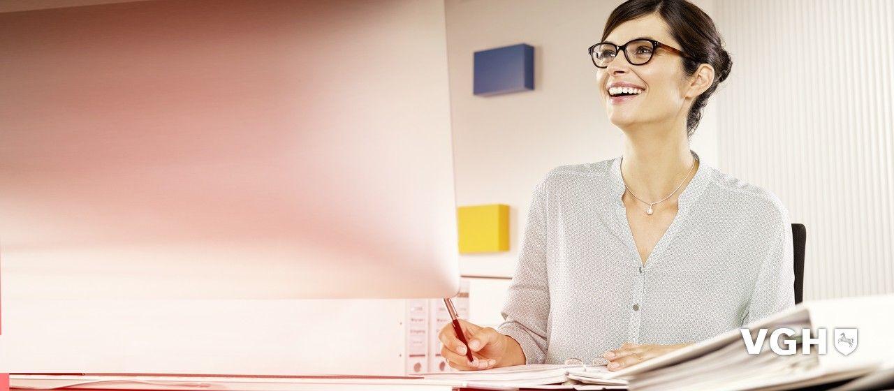 Junge Frau mit Brille am Schreibtisch