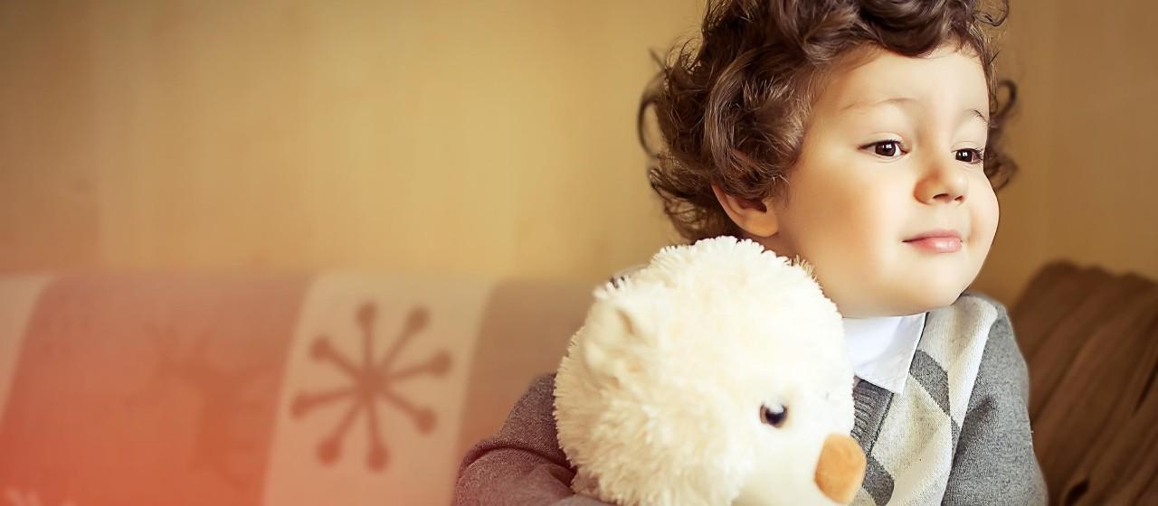 Kleiner Junge mit Kuscheltier auf einem Sofa