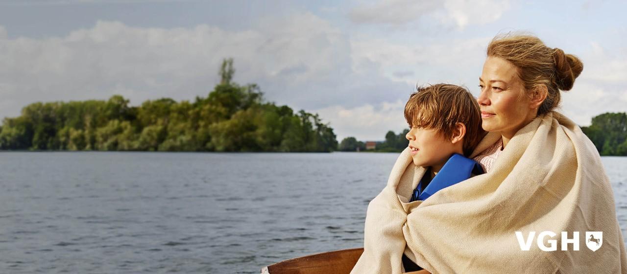 Frau mit Kind unter einer Decke auf einem Boot