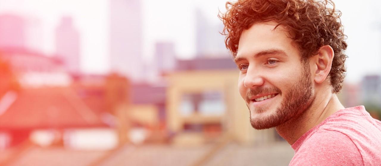 Junger Mann schaut über die Dächer einer Stadt