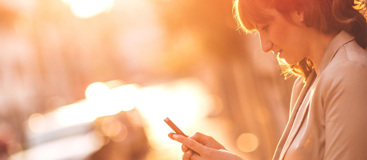 Frau mit Smartphone auf Gehweg