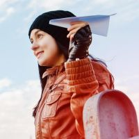 Frau mit Papierflieger auf Brücke